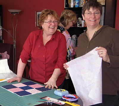 Lois shows Kirsten how to prepare for quilting.